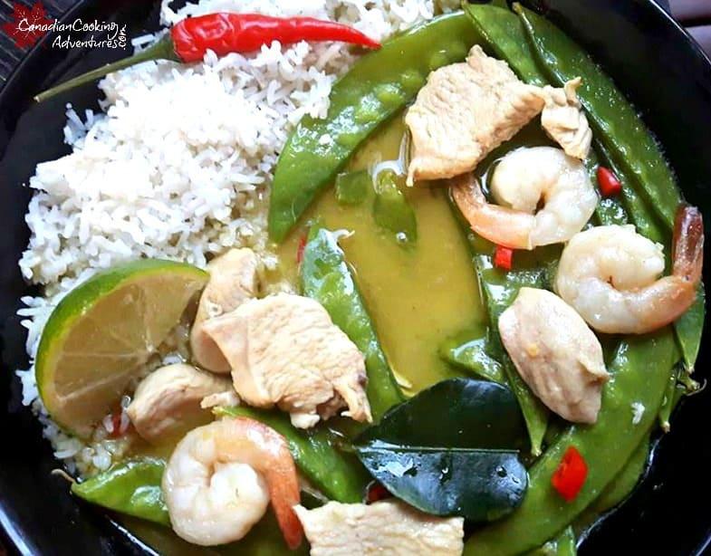 Green Thai Chicken Curry + Snow Peas in a black bowl