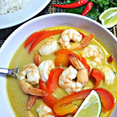 Red Thai curry with Shrimp and Red Peppers in a white bowl and some limes